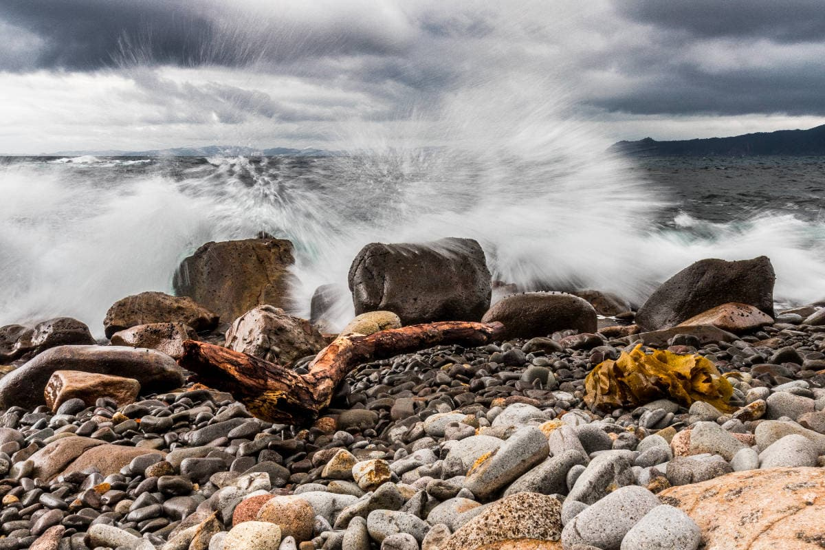 the ocean splashes over two large rocks on a rocky shore