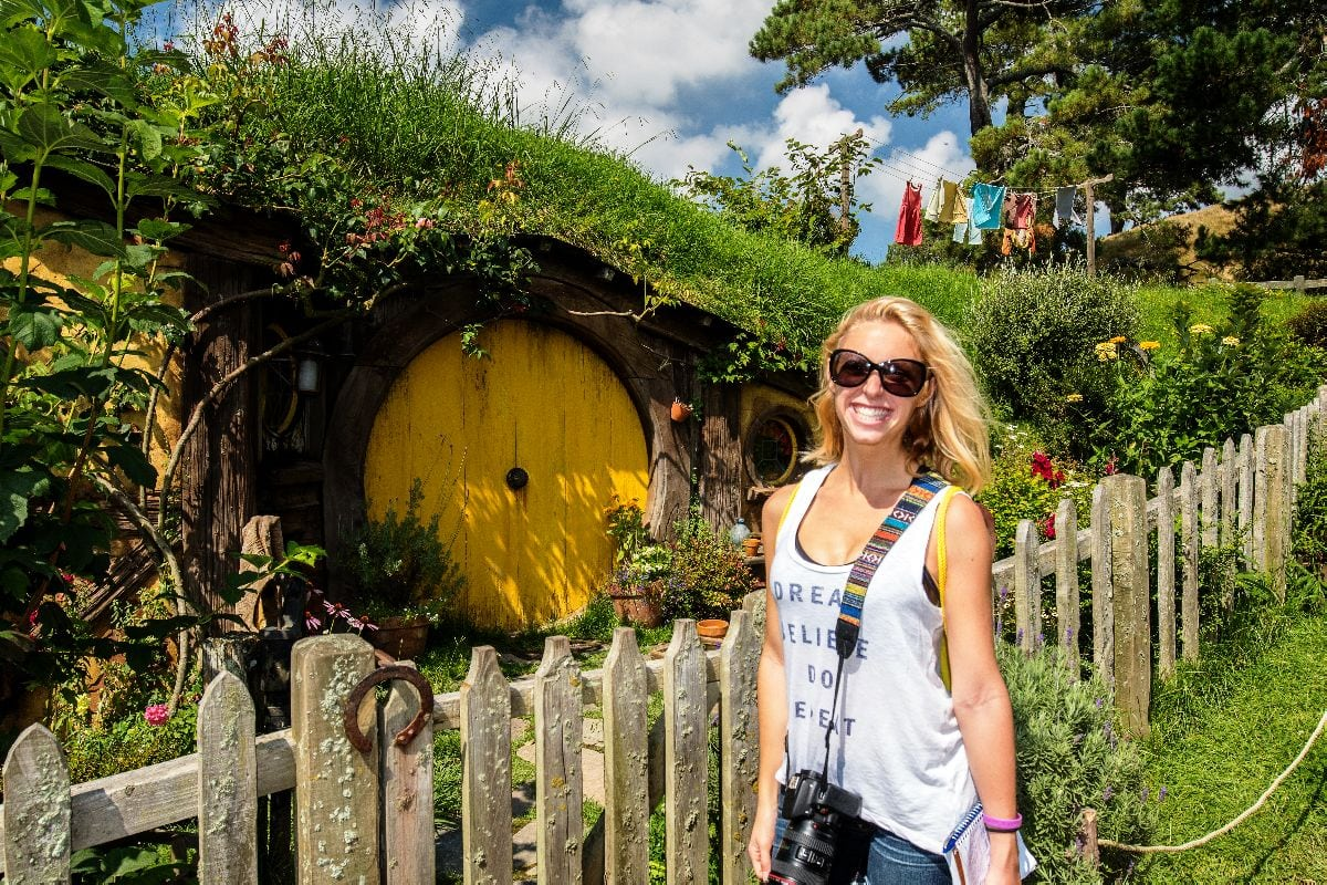 blonde girl in white shirt stands in front of hobbit house with a yellow door