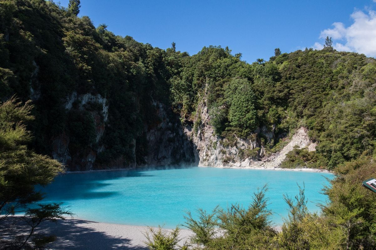 turquoise blue sulfuric lake surrounded by trees