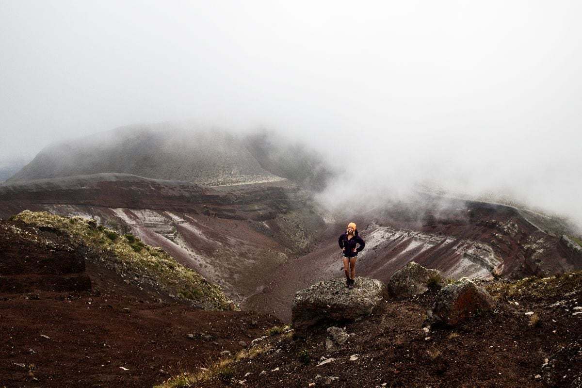 girl stands in shorts and a purple rain jacket with an orange beanie in front of a volcano