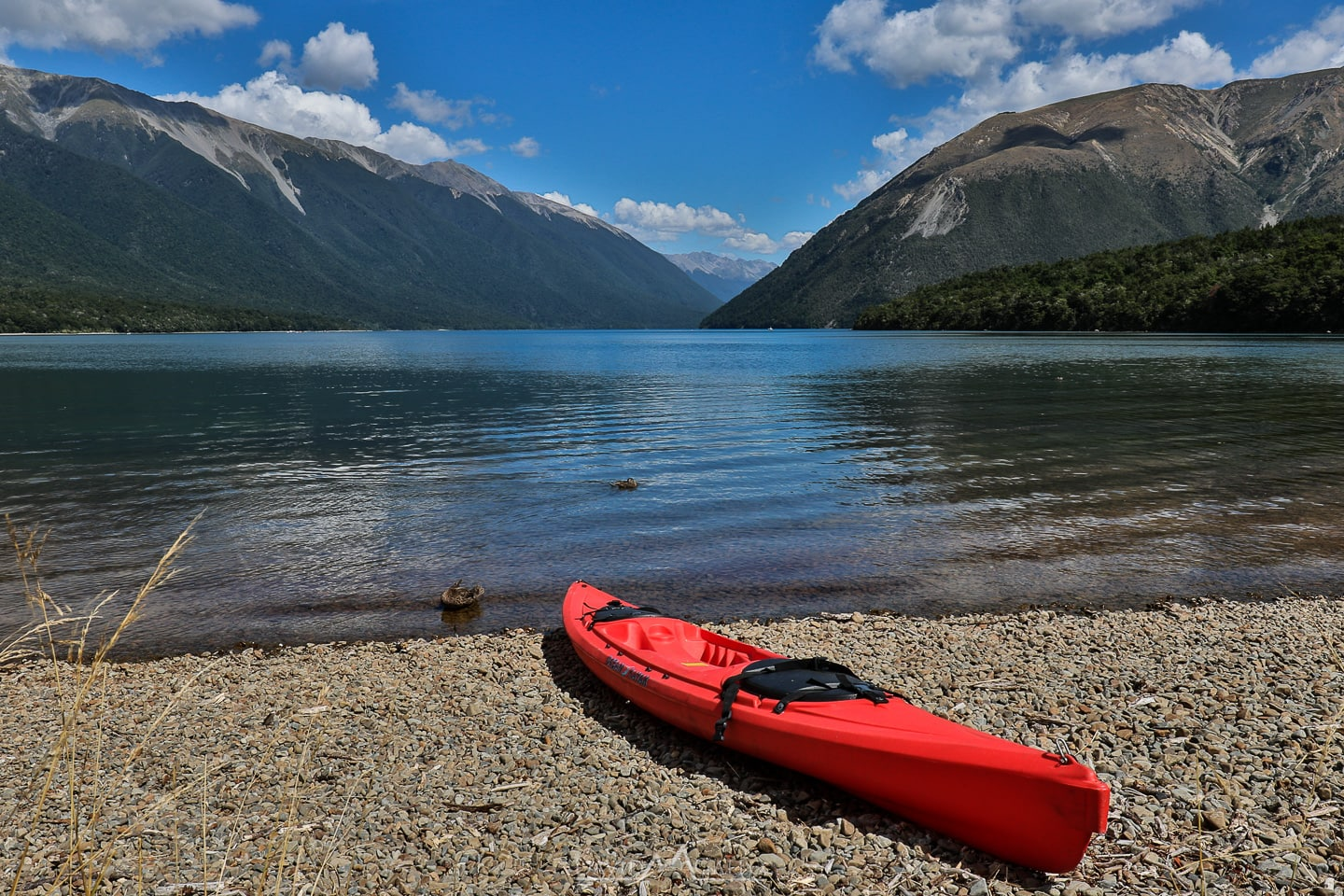 a red kayak sits on the shore of a lake