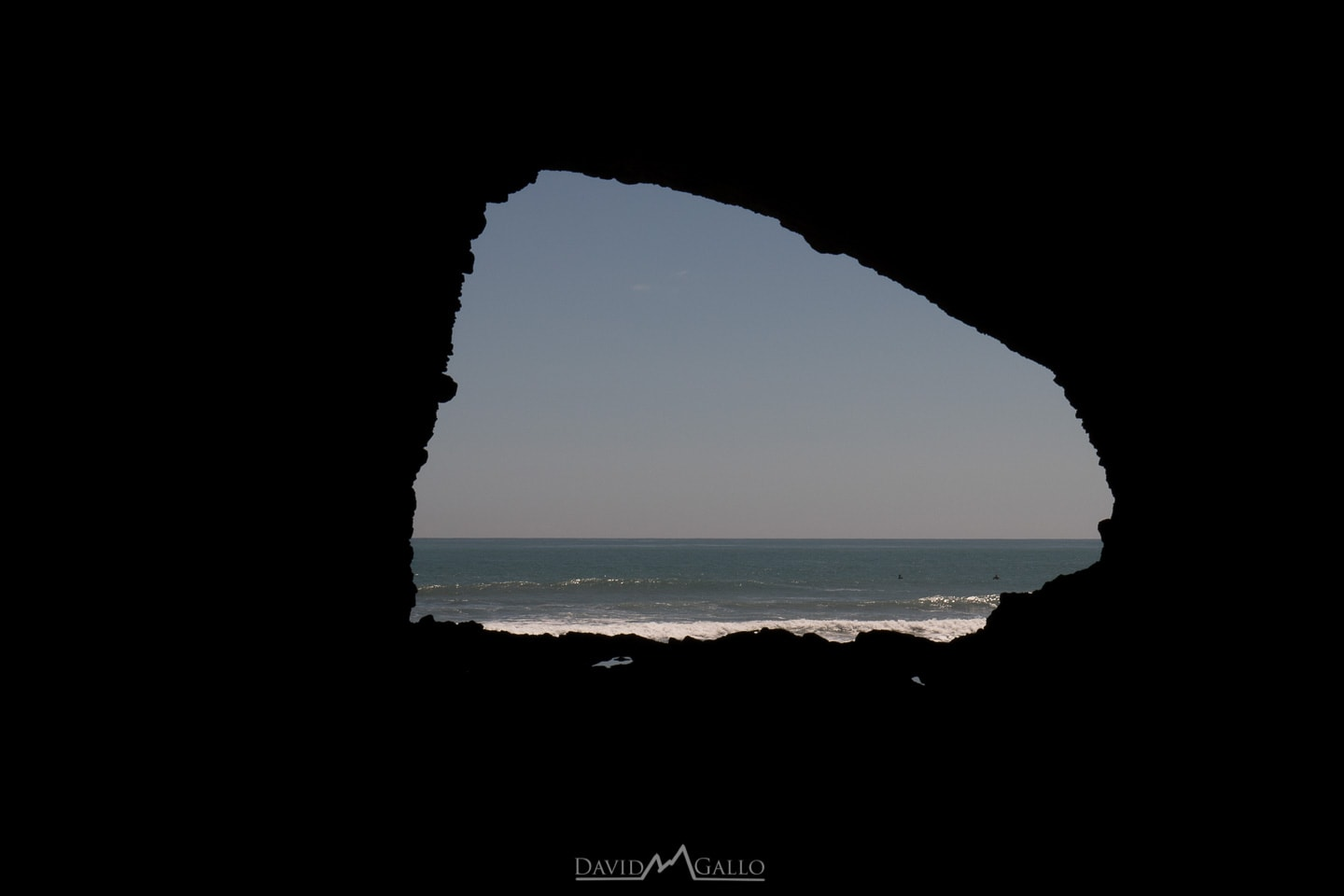 a silhouetted cave frames the ocean