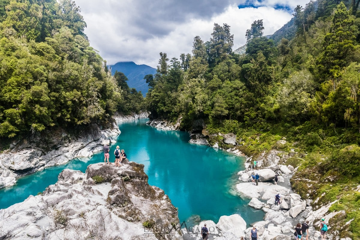 a turquoise blue lake is surrounded by rocks and green pine trees