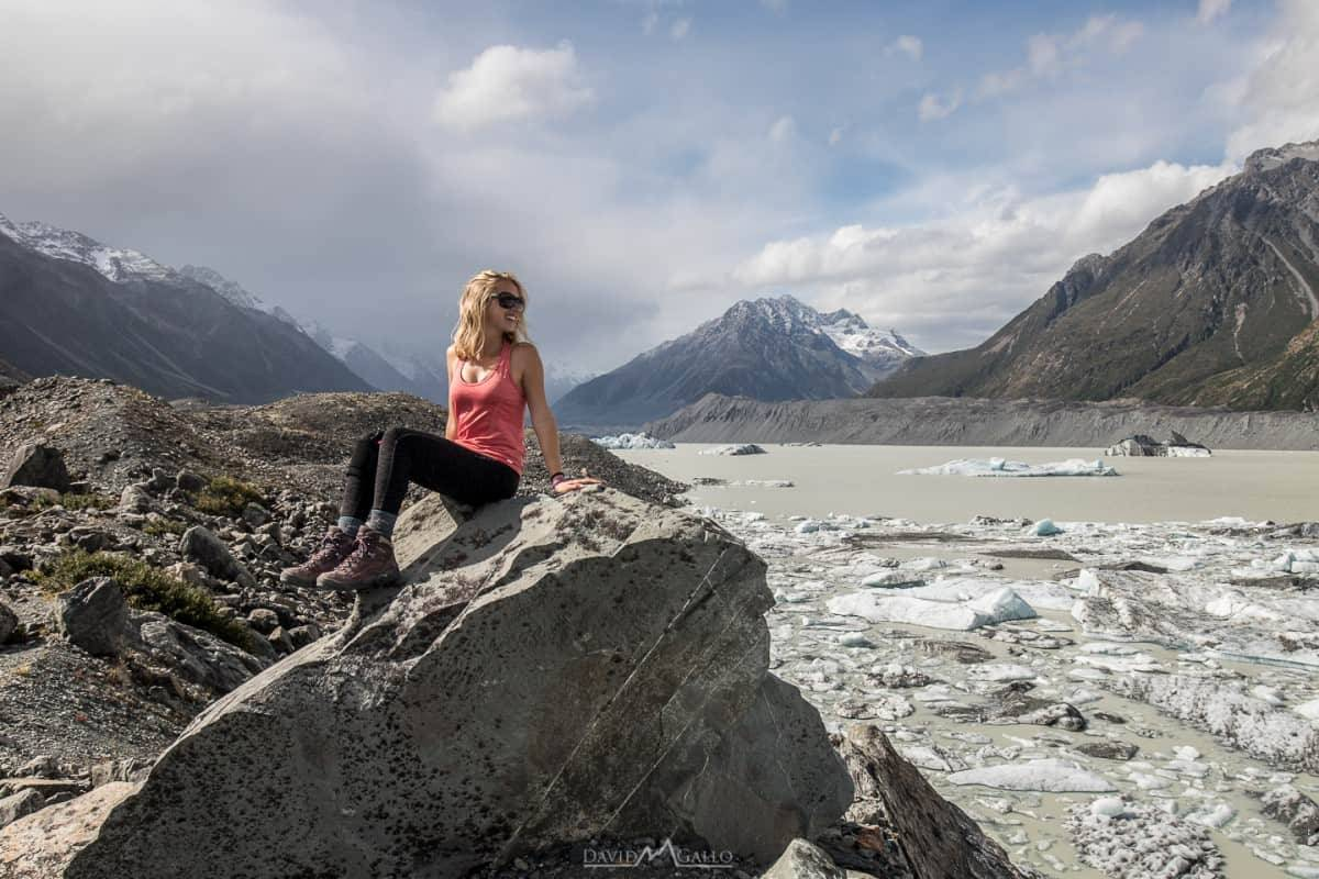 girls sits on a rock beside a lake filled with ice bergs
