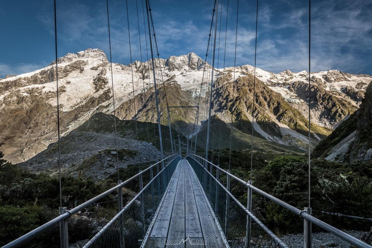 a suspension bridge frames snow covered mountain peaks