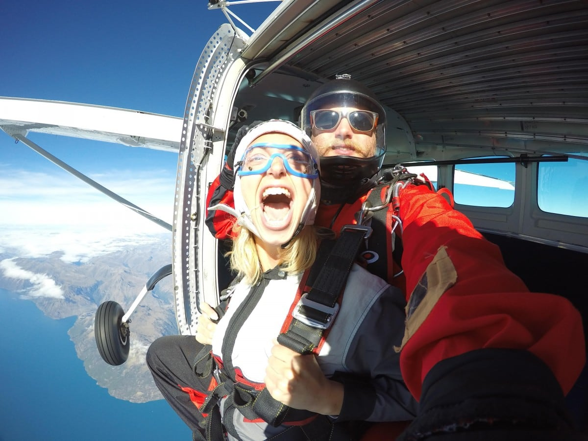 girls sits on edge of plane with mouth open, excited to skydive