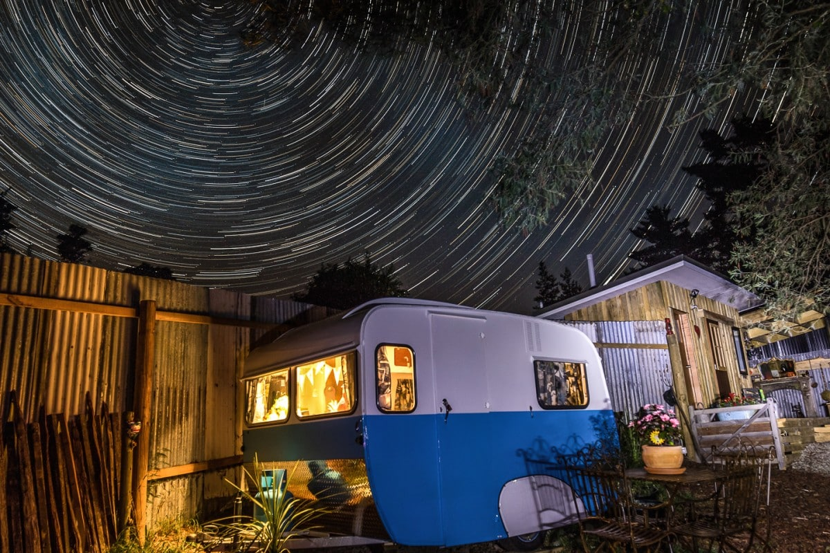 a blue and white caravan in the foregeound with a circular star trail in the background
