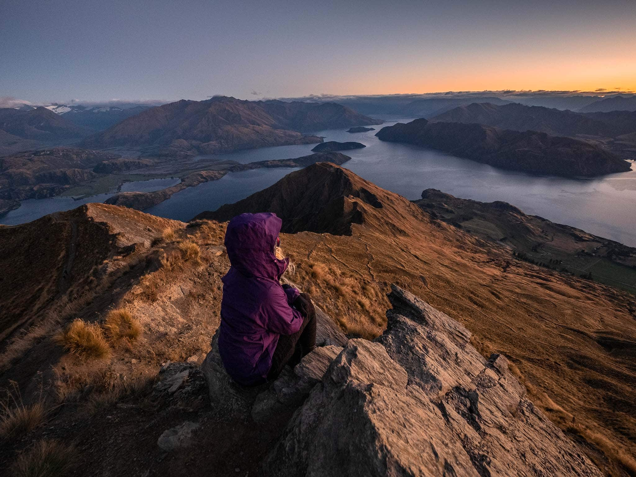 girl with purple jacket sits atop a mountain watching sunrise over a lake