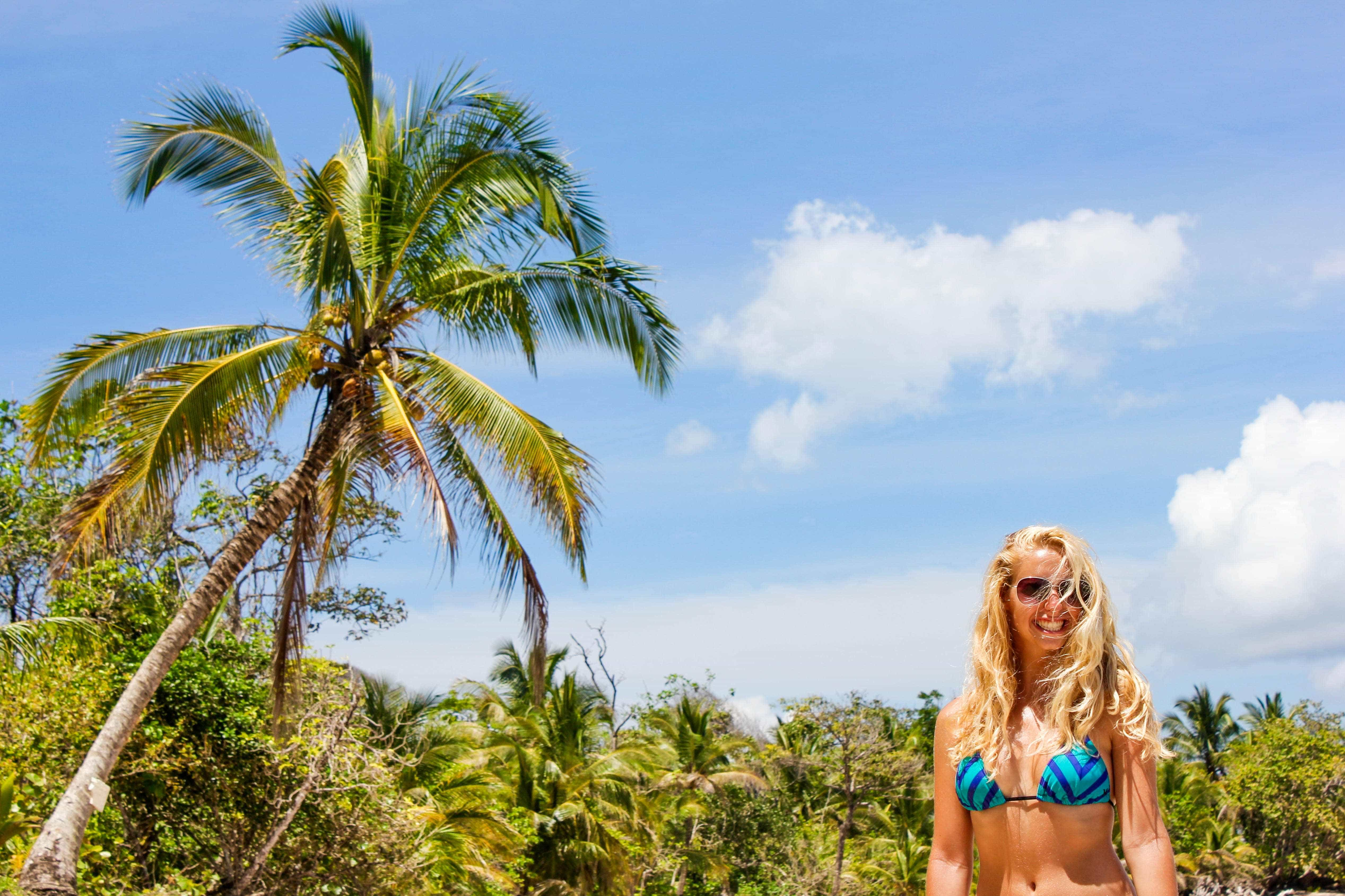 girl on beach with palm tree in bocas del toro panama