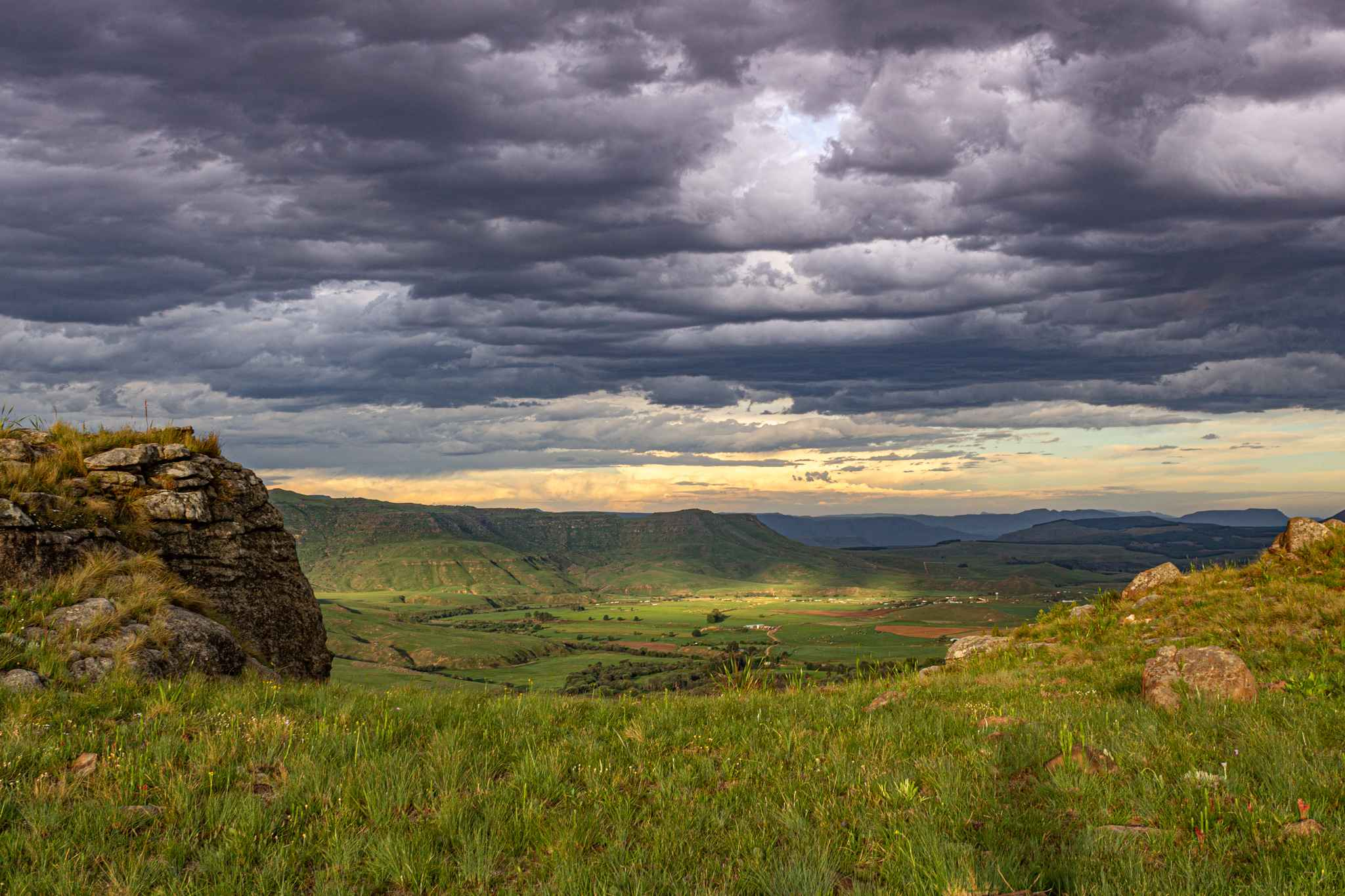 a beautiful sunset of purples and oranges over a green valley in the drakensberg mountains - a beautiful night on a south africa vacation