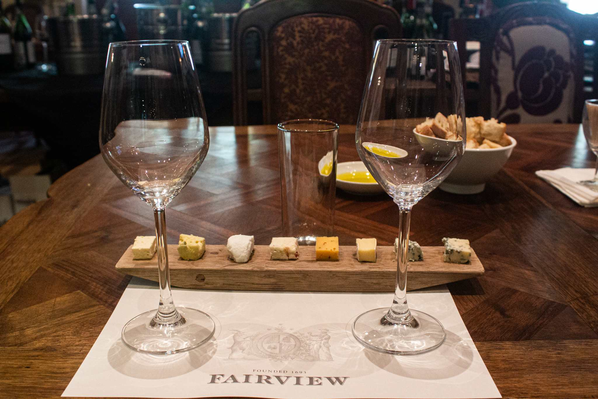 two wine glasses and eight different pieces of cheese for a wine and cheese pairing; who doesn't want to indulge in quality wine and cheese on their south africa vacation?