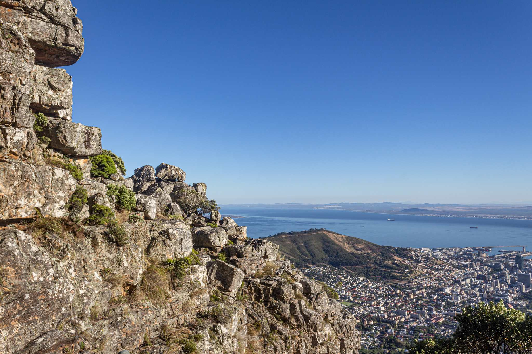 a rock scramble up table mountain offers beautiful views of the ocean and cape town below; your south africa vacation wouldn't be complete without a trip up table mountain!