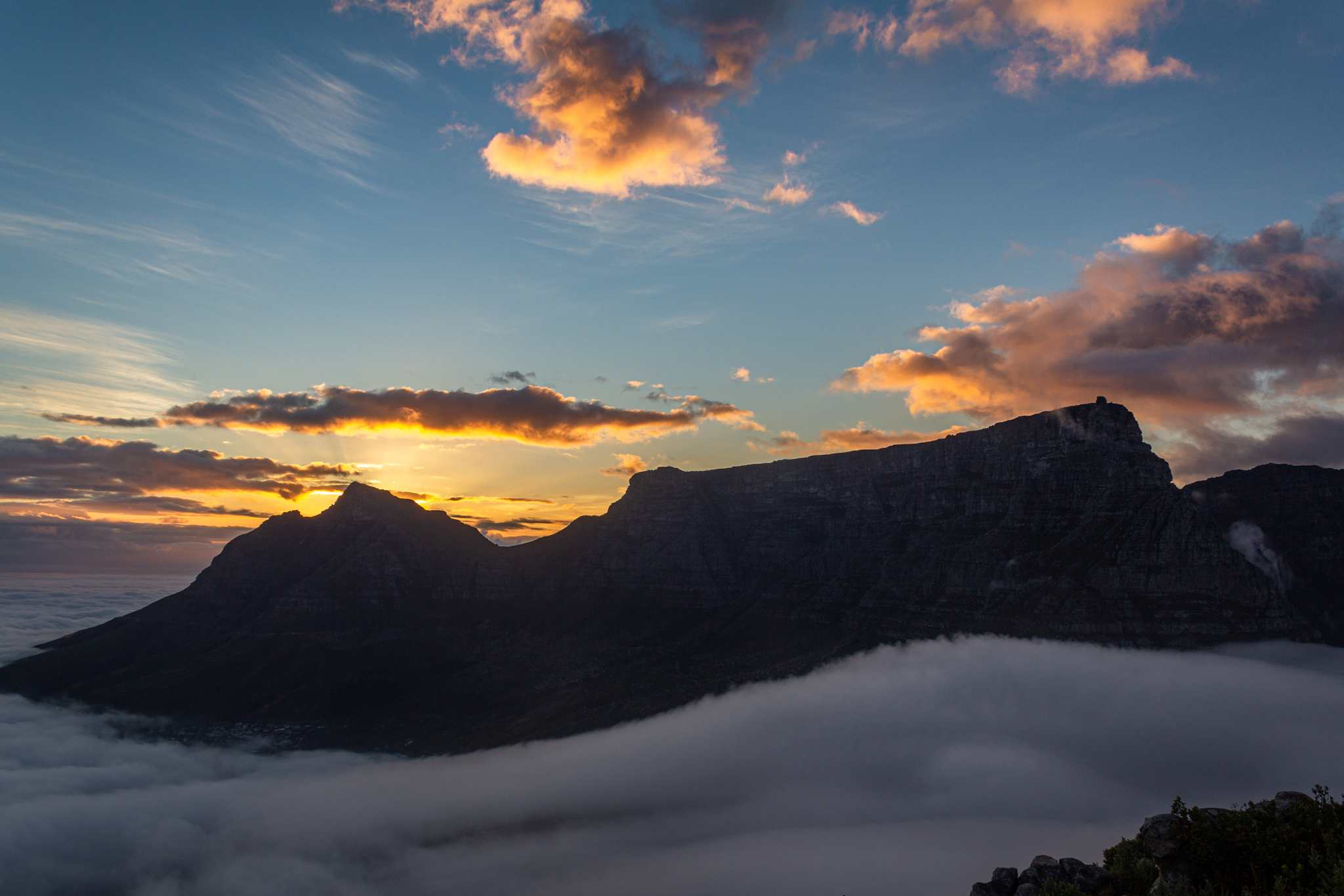 table mountain at sunrises with a thick fog at the base of the mountain; the sunrise is yellow and orange