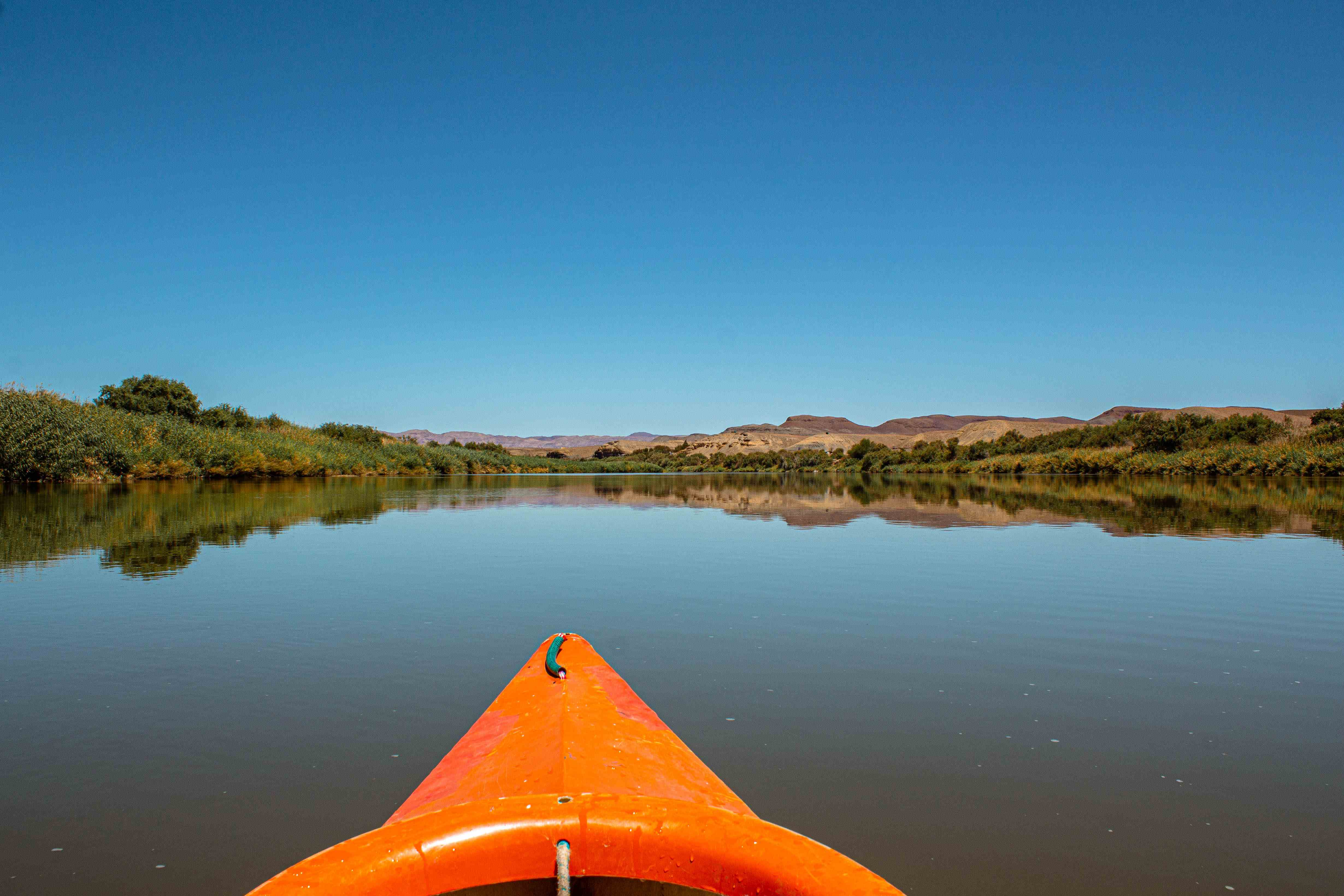 orange canoe in the middle of the orange river in namibia. mountains with reflections in the distance.