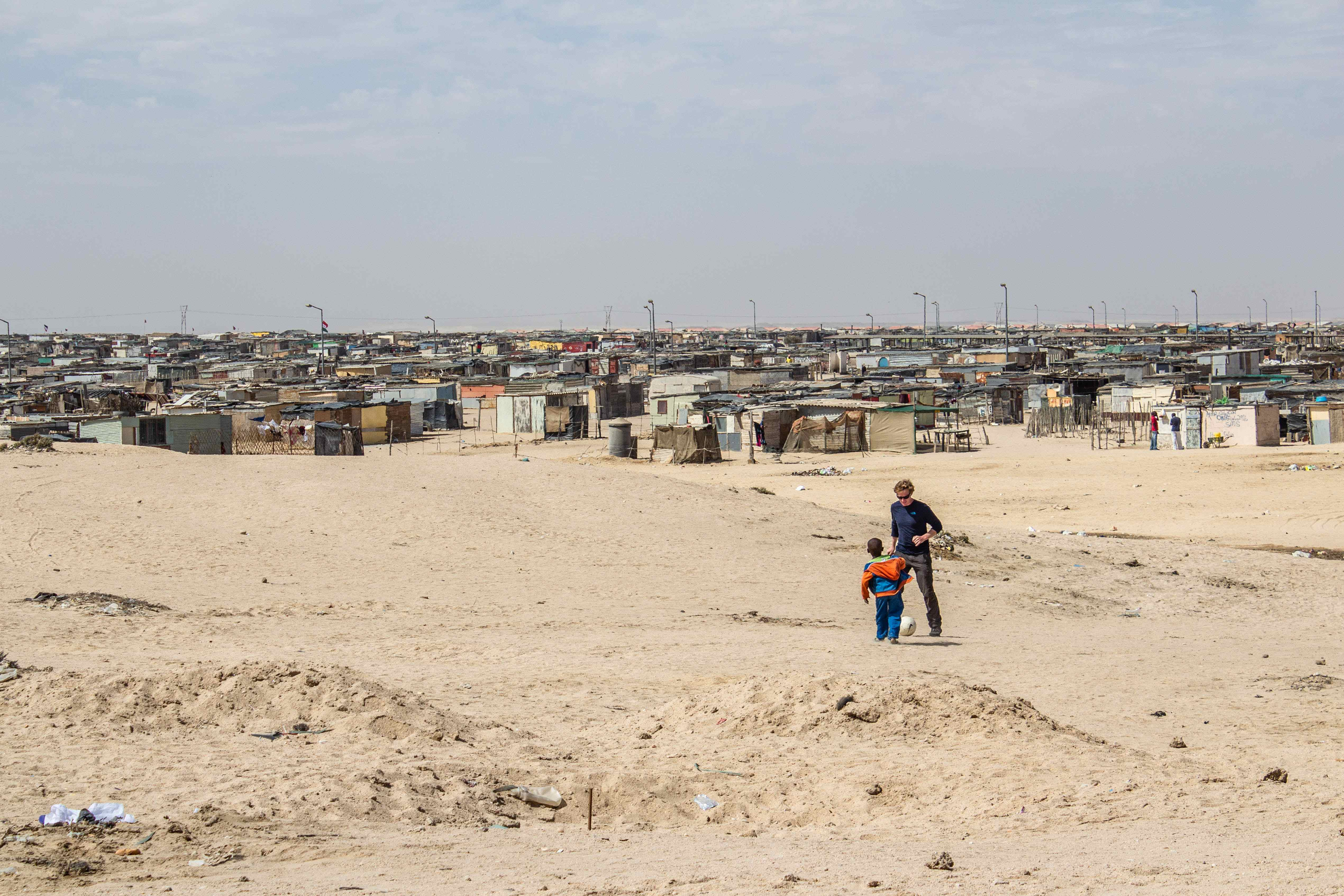 township in namibia with a man and boy playing soccer in the foreground
