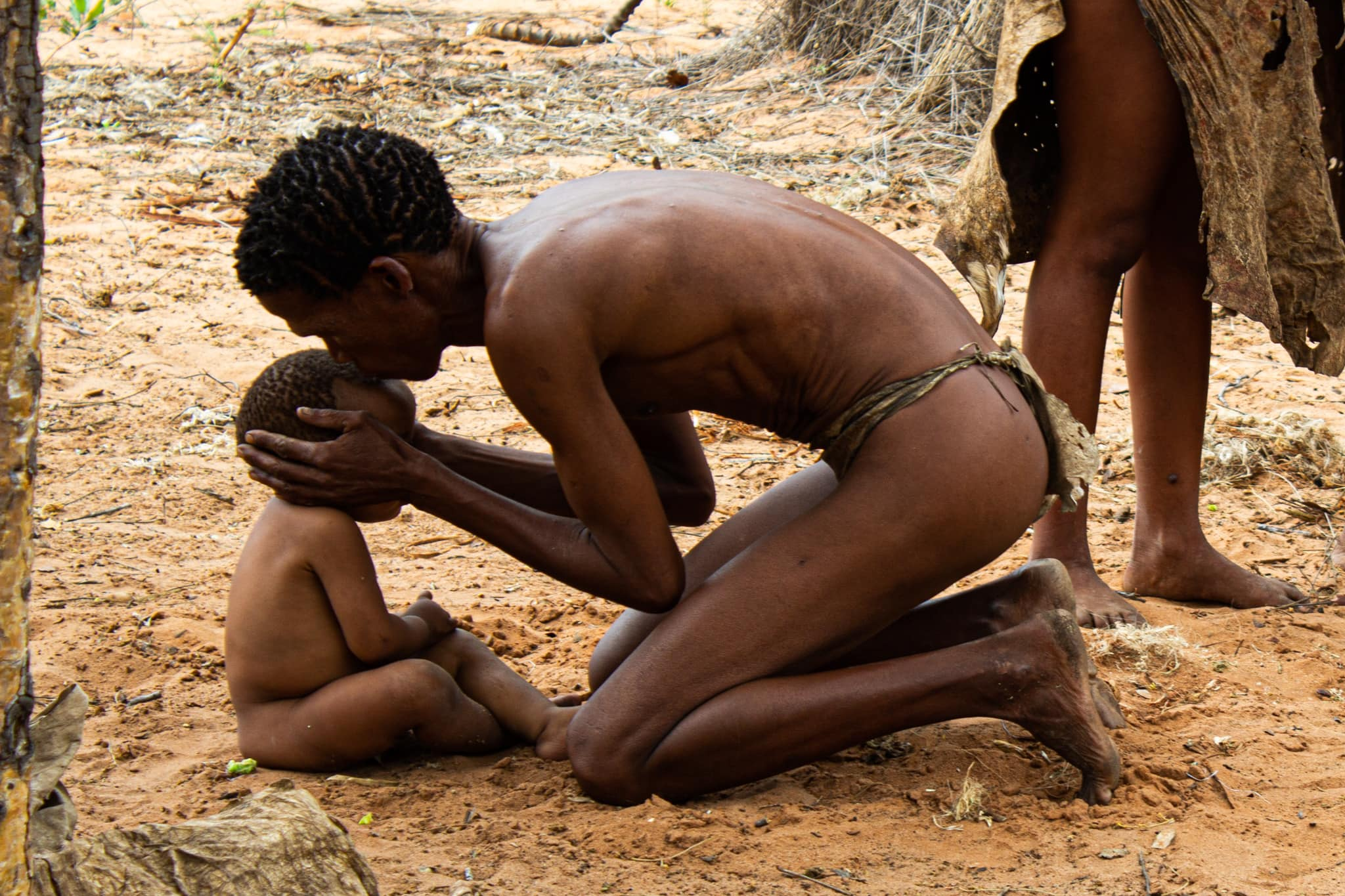man wearing traditional clothing of the san bushmen kisses baby on head