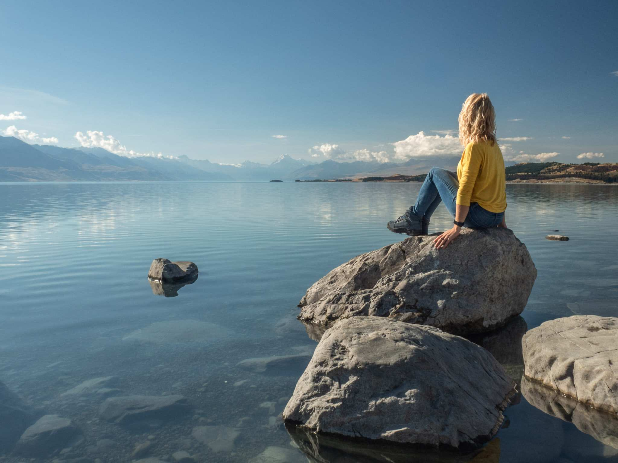 blonde girl in yellow shirt and jeans perches on rock in water overlooking mountains in the distance