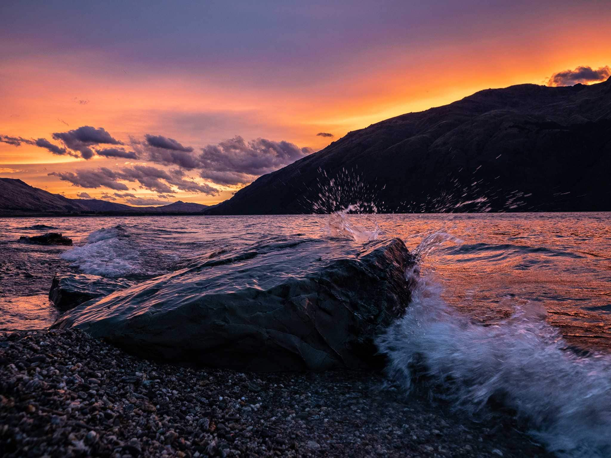 water splashes on large rock in foreground during sunset