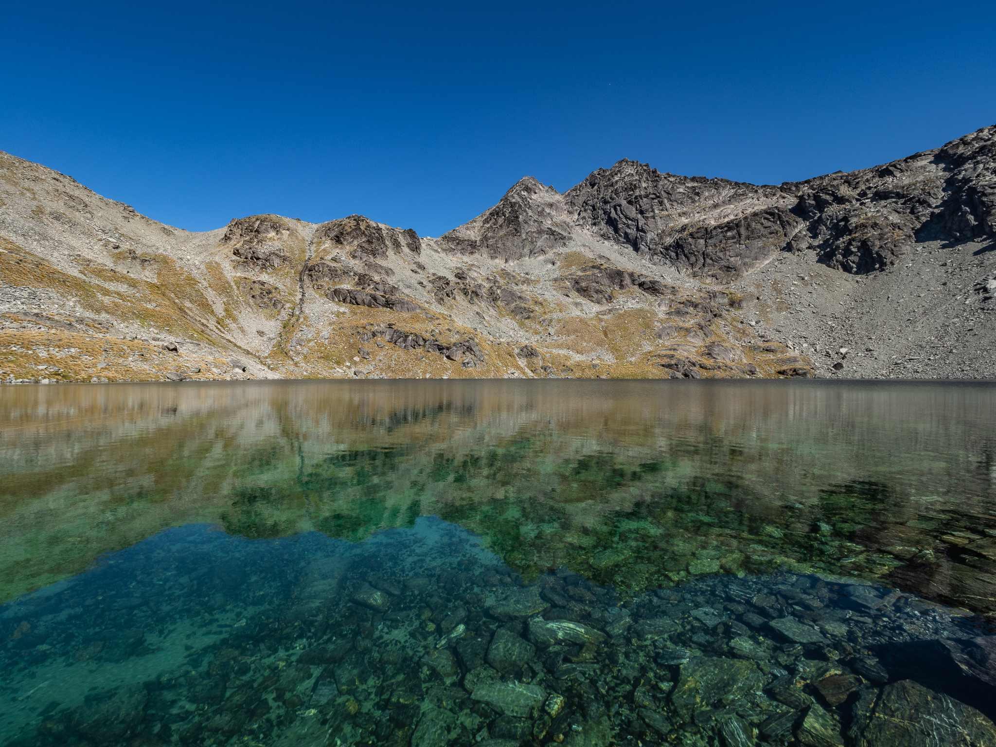 beautiful mountain peaks reflect on the alpine lake below