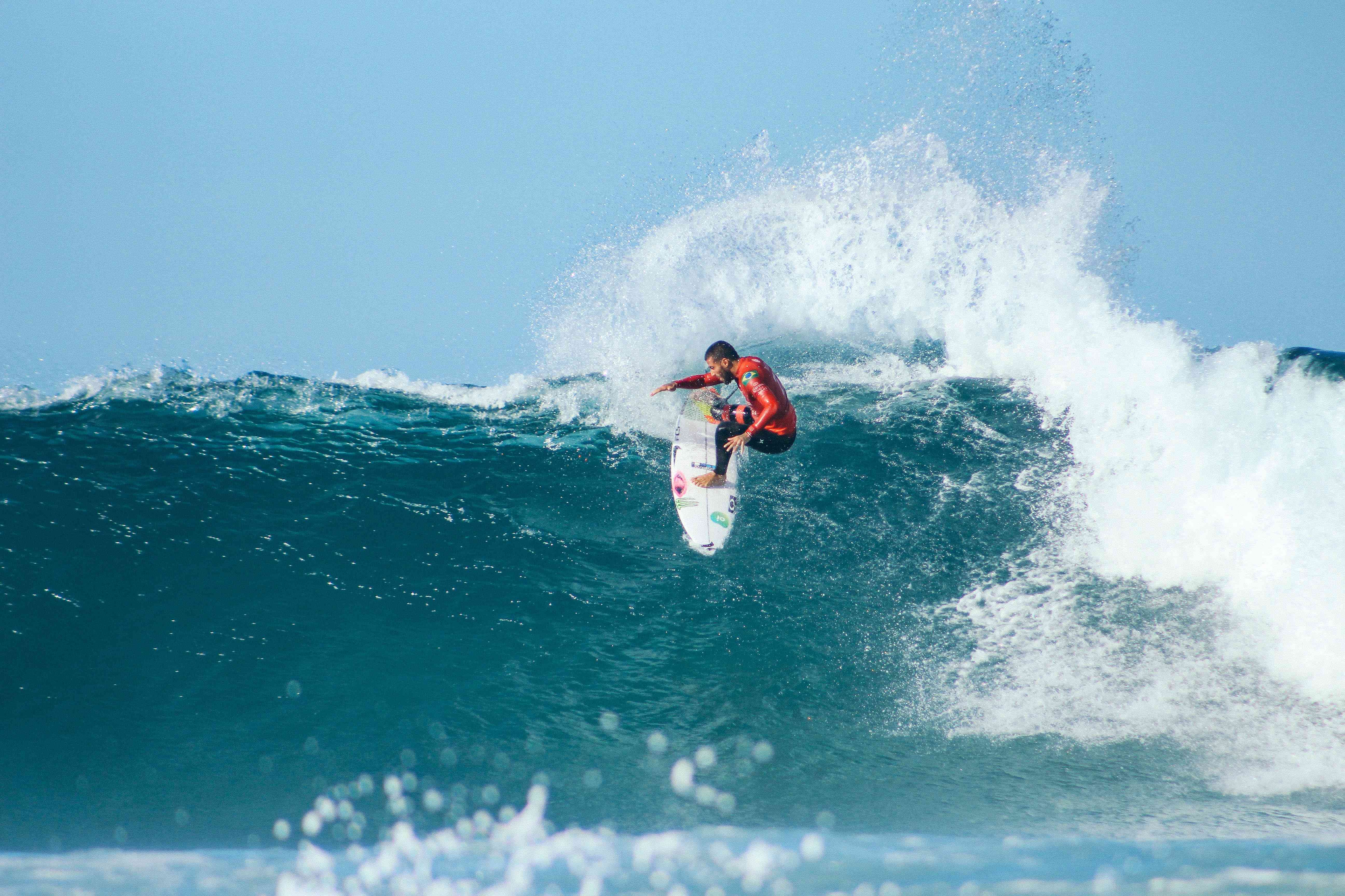 a man in a red rash guard catches a waves