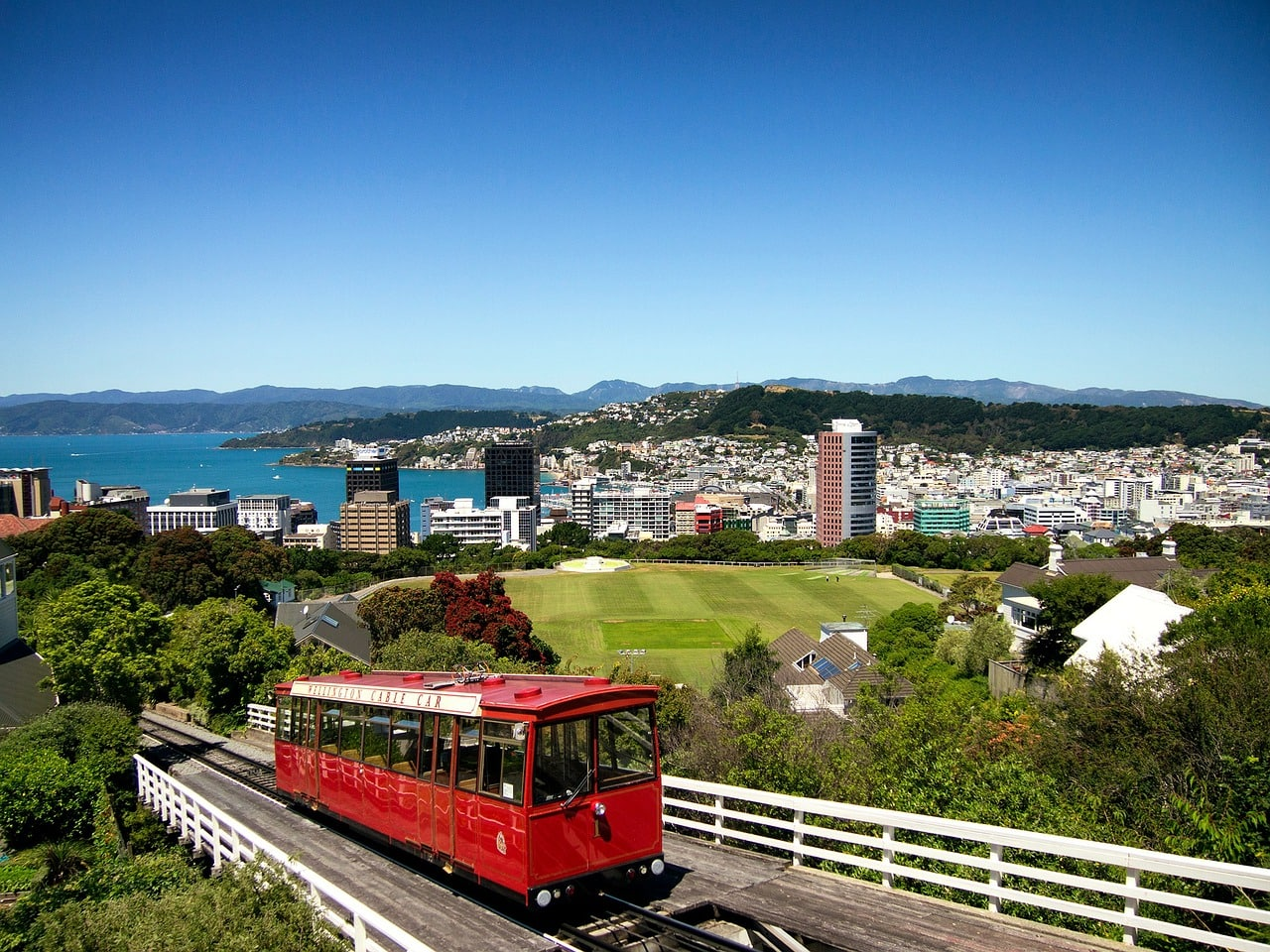 red cable car goes up to a viewpoint overlooking wellington, new zealand