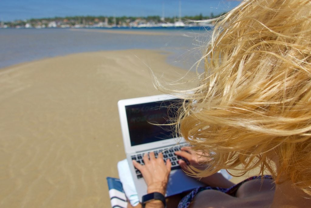 girl works on laptop at the beach