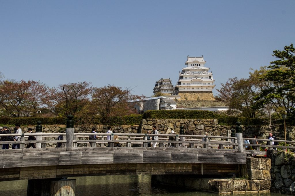 an intricate white castle with a pedestrian bridge in the foreground in himeji - places to visit in japan