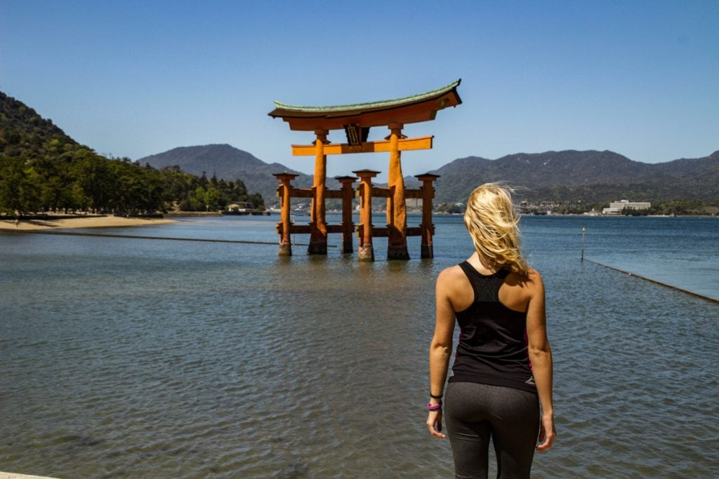 girl stands in front of the tori gate in miyajima - places to visit in japan