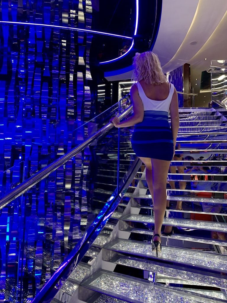 girl walks up shimmering stairs on a cruise ship in her black stilettos - travel essentials