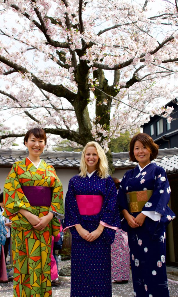 three ladies standing in front of a cherry blossom tree wearing kimono - things to do in japan