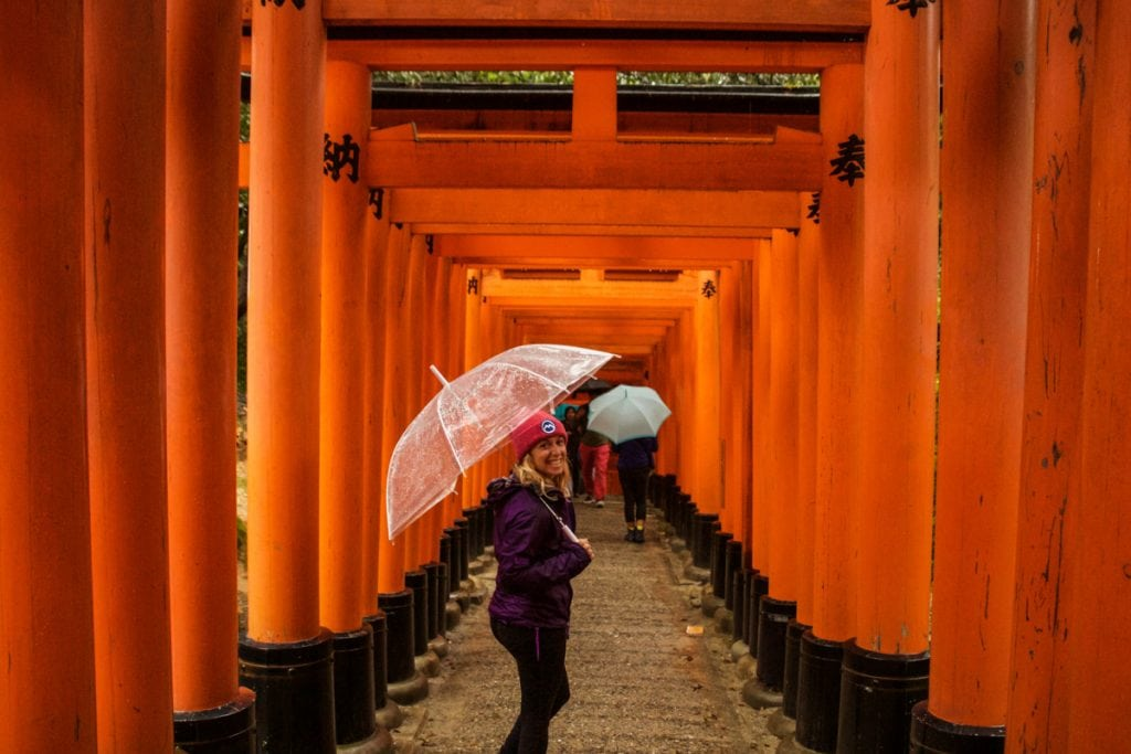girl walks through the fushimi inari shrine in kyoto - places to visit in japan