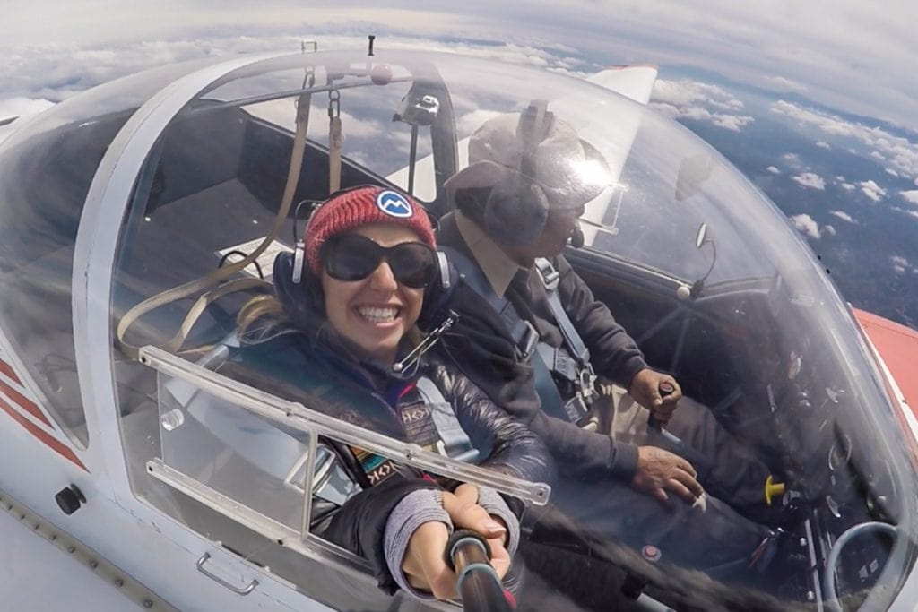 girl in hat and jacket in a small glider over the japanese alps - things to do in japan