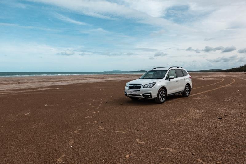 a car drives on a lone beach