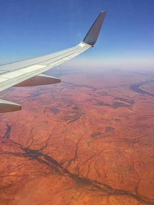 airplane wing over australia's red desert