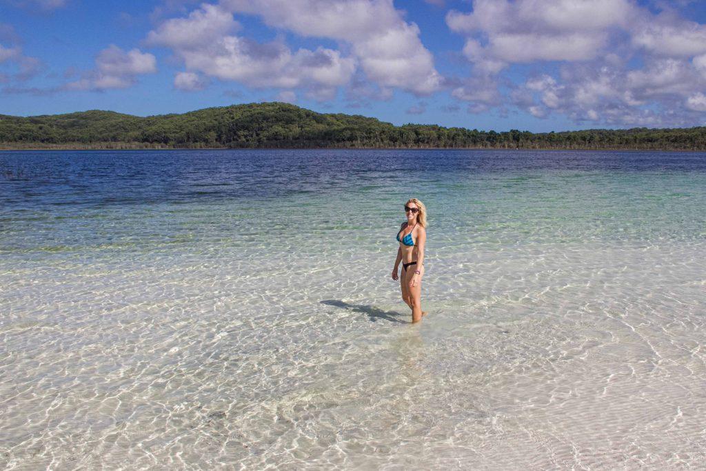girl stands in crystal clear water wearing a bikini