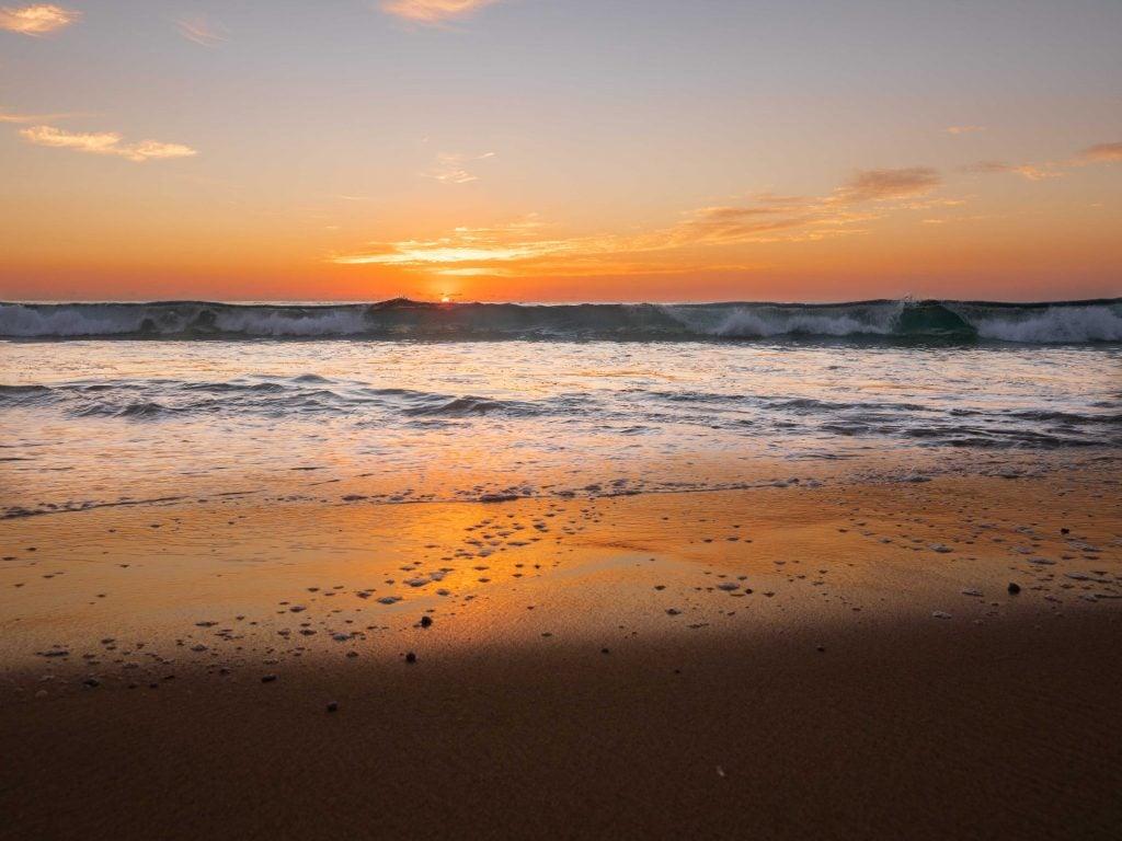 a beautiful orange sunrise behind crashing waves - things to see in australia