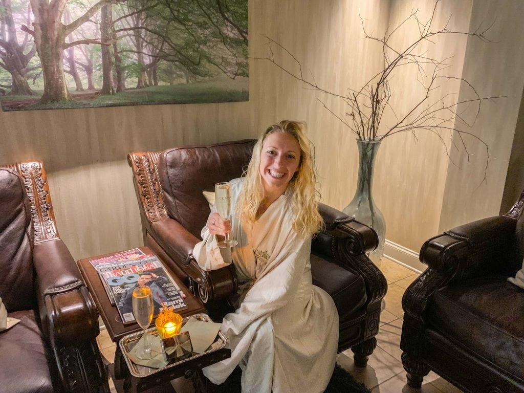 girl sits in plush robe holding champagne after a massage
