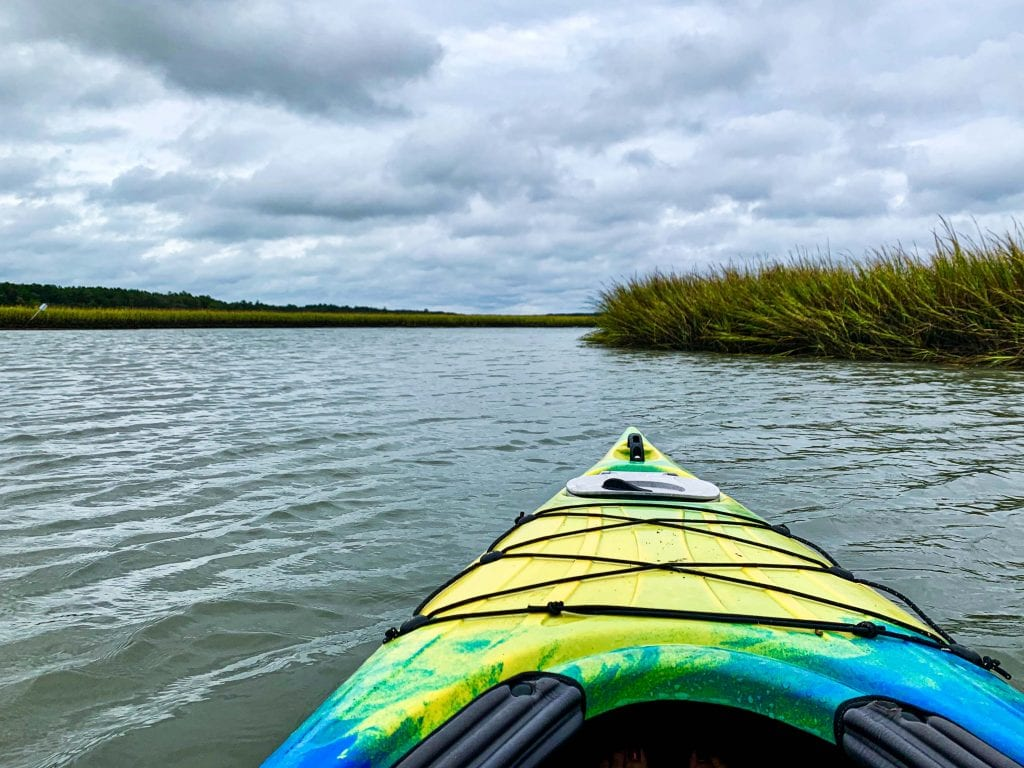 a yellow and green kayak in the marsh