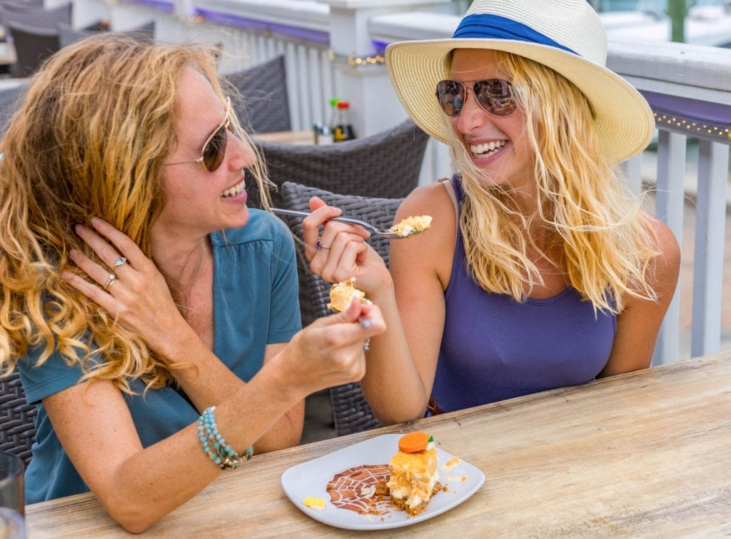 a mother and daughter laugh as they share a piece of pumpkin cheesecake