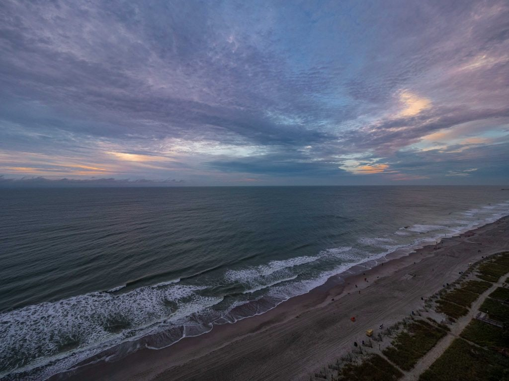 sunrise from a hotel balcony overlooking the ocean and beach below