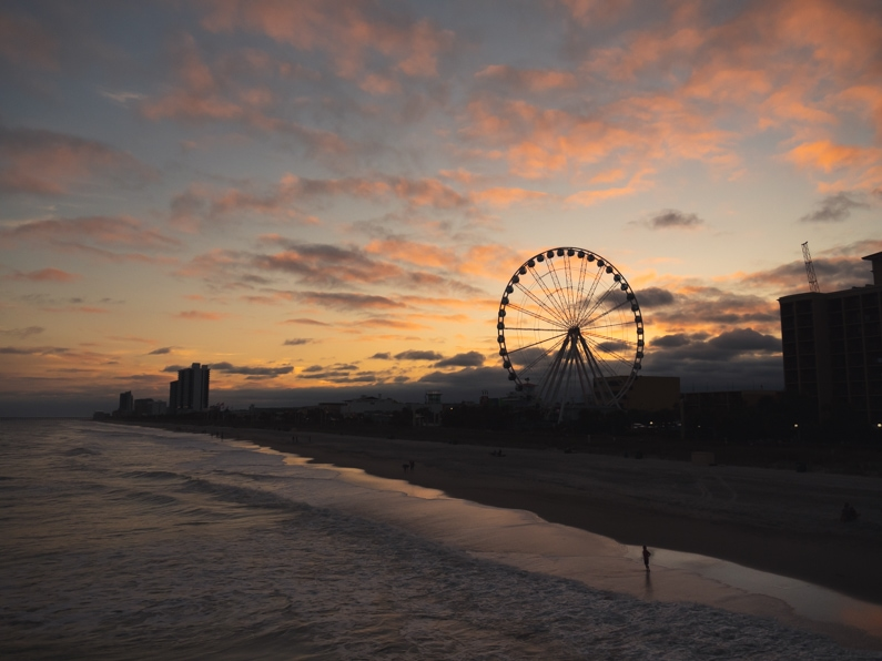 the sun sets in pinks and oranges behind myrtle beach's skywheel