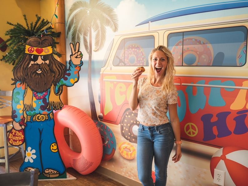 girl stands with a hippie poster holding a little donut