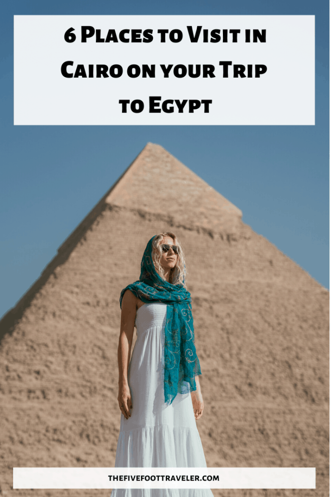 a girl in a white dress and blue headscarf stands in front of a pyramid