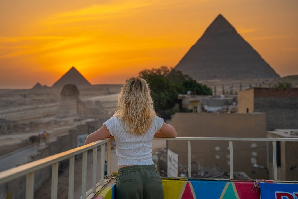 girl leans on railing of the rooftop of her hotel overlooking the pyramids and sphinx at sunset on her trip to egypt