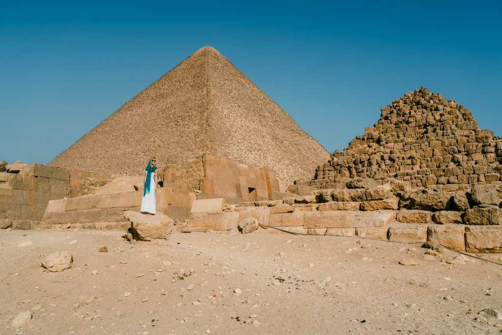 a girl stands in front of the great pyramid of giza wearing a white dress and turquoise scarf on her egypt pyramids tour