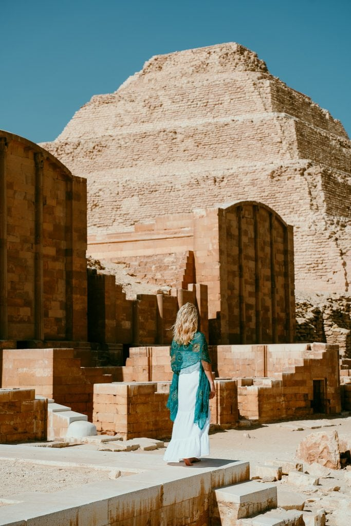 a girl stands in front of the oldest step pyramid in the world at saqqara as part of her egypt pyramids tour