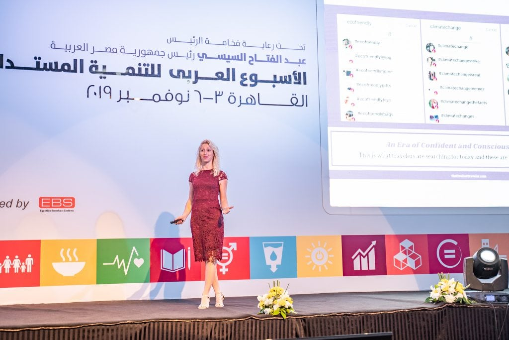 girl stands on stage discussing responsible tourism