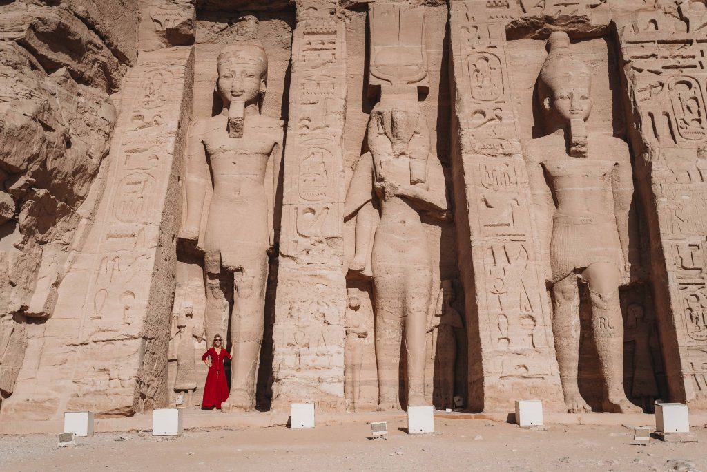 girl stands next to colossal statue in front of the small temple at abu simbel