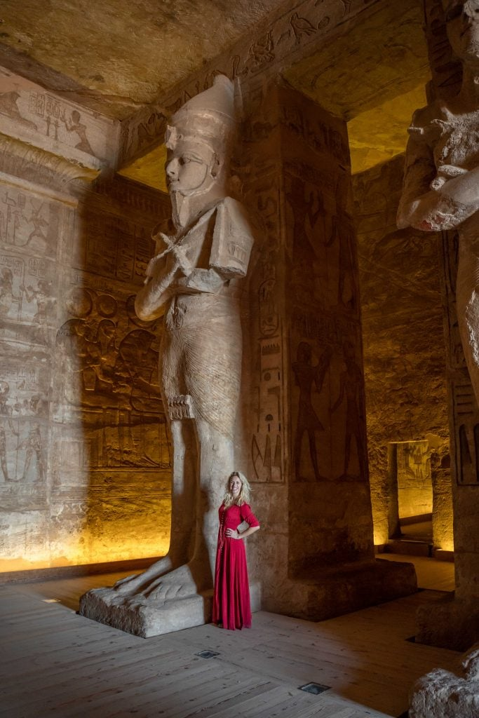 girl in red dress stands next to a colossal statue inside abu simbel