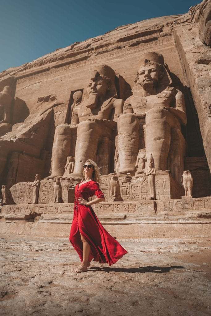 girl stands in front of colossal statues on her abu simbel tour